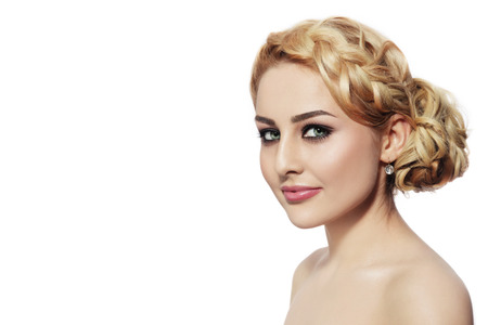 Portrait of young beautiful blonde woman with stylish prom hairdo over white background