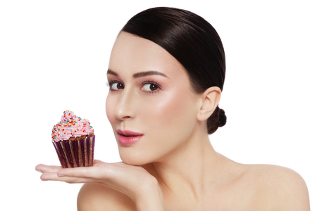 guilty pleasure: Young beautiful girl with excited expression and tasty cupcake in her hand over white background, copy space Stock Photo