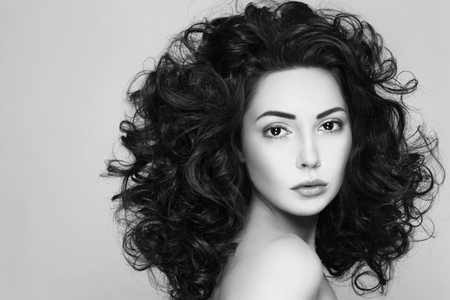 perming: Black and white shot of young beautiful woman with long curly hair