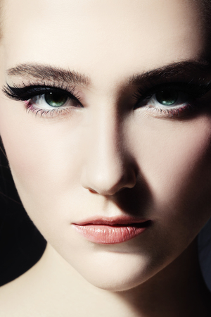 cat eye: Close-up portrait of young beautiful girl with fancy cat eye make-up