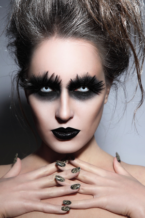 Woman with stylish fancy gothic Halloween make-up and manicure