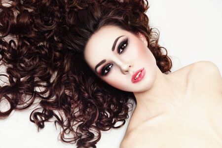 perming: Young beautiful woman with fresh make-up and long curly hair