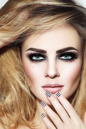 연기가 자욱한 눈과 세련된 스트라이프 매니큐어와 젊은 아름 다운 섹시 한 여자의 초상화