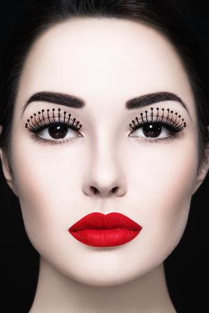 pestaÑas postizas: Primer plano retrato de mujer joven y hermosa con las pestañas falsas de lujo y lápiz labial rojo mate