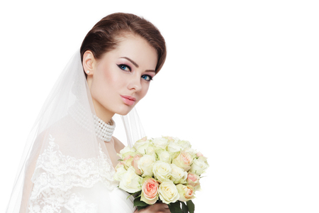 Young beautiful bride with stylish make-up and hairdo holding bouquet over white background, copy space Stock Photo