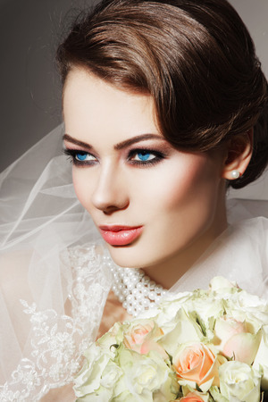 Portrait of young beautiful woman with bridal veil and bouquet of roses