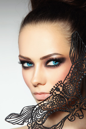 smoky eyes: Close-up portrait of young beautiful woman with smoky eyes and lacy black mask