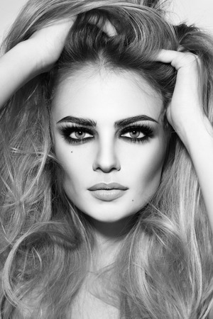 Black and white shot of young beautiful girl with long hair and smoky eyes