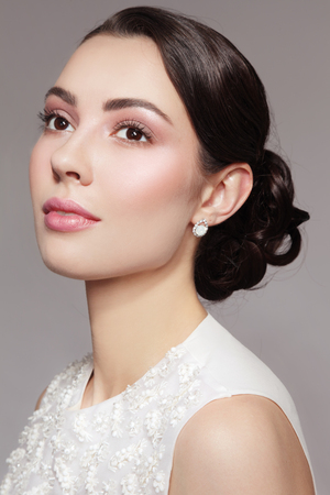 cheekbones: Portrait of young beautiful dreamy bride with stylish make-up and prom hairdo