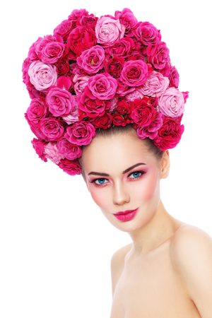 Young beautiful woman with stylish make-up in fancy vintage style wig of pink roses over white background Stock Photo