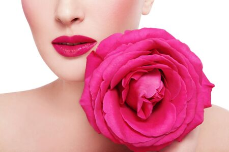 Close-up shot of womans lips with fuchsia lipstick and beautiful hot pink rose over white background