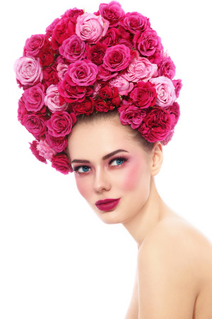 Young beautiful woman with stylish make-up in fancy vintage style wig of pink roses looking upwards, over white background