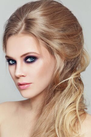 Portrait of young beautiful woman with smoky eyes make-up and stylish messy hairdo