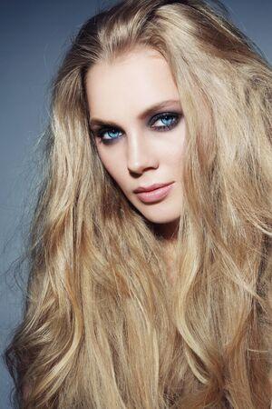 cabello rubio: Mujer hermosa joven con el pelo rubio largo y ojos ahumados maquillaje elegante