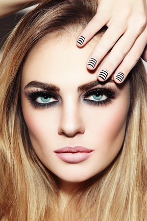 Portrait of young beautiful girl with smoky eyes and stylish striped manicure