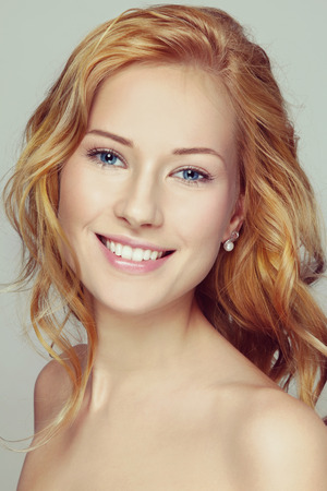 red hair girl: Portrait of young beautiful happy smiling girl with curly red hair and clean make-up