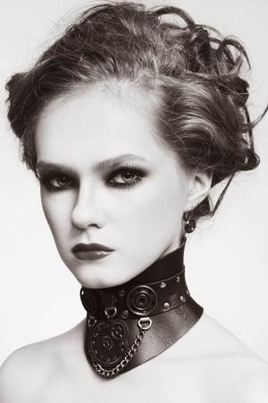 Sepia portrait of young beautiful girl with stylish hairdo and fancy steampunk collar photo