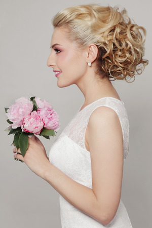 Young beautiful blonde slim bride with stylish prom hairdo and bridal bouquet Stock Photo