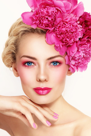 Portrait of young beautiful healthy blonde woman with clean make-up and pink peony flowers in her hair