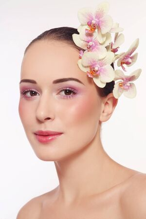 Portrait of young beautiful happy healthy woman with fresh make-up and white orchid