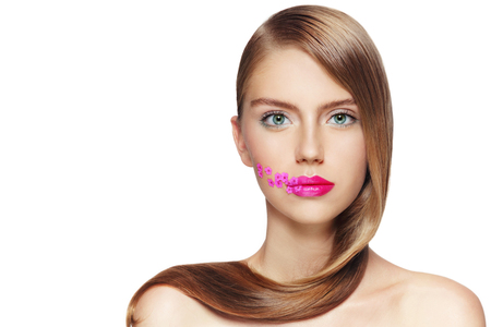 gloss: Portrait of young beautiful girl with fuchsia lipstick and small pink flowers on her face over white background, copy space Stock Photo