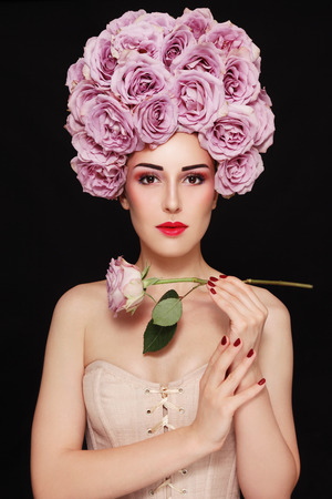 Young beautiful woman in fancy vintage style wig of roses and corset Stock Photo