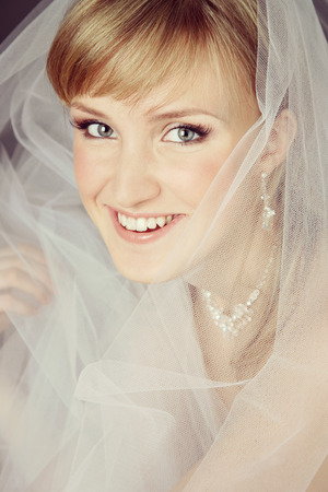 Vintage style portrait of young beautiful happy smiling bride with bridal veil photo
