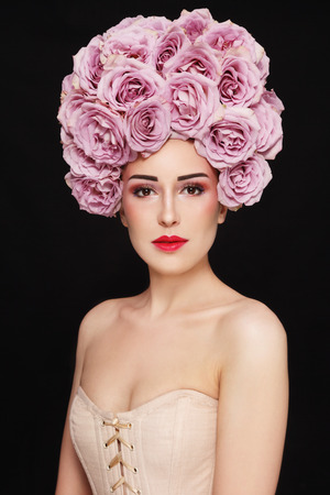 Young beautiful girl in corset and vintage style wig of roses