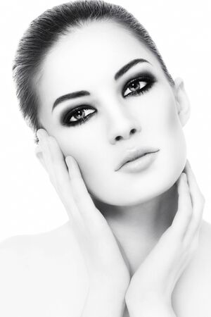 High key black and white portrait of young beautiful healthy woman with smoky eyes make-up touching her face photo