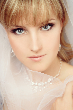 Vintage style close-up portrait of young beautiful bride with stylish make-up and bridal veil photo