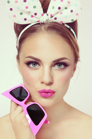 hot pink: Vintage style portrait of young beautiful sexy girl with fancy hairband and hot pink sunglasses in her hand Stock Photo