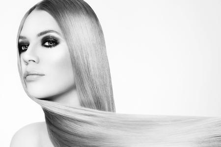 Schwarz-Weiß-Porträt der schönen jungen Frau mit rauchigen Augen und langen glatten Haaren