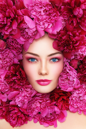 hot pink: Portrait of beautiful blue-eyed woman with hot pink peonies around her face