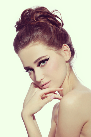 Vintage style portrait of young beautiful woman with fancy cat eye make-up and stylish hairdo