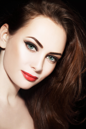 red winged: Portrait of young beautiful grren-eyed woman with winged eyes make-up and red lipstick
