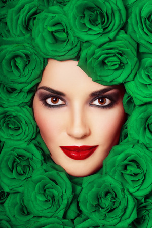 Vintage style close-up portrait of beautiful young girl with smoky eyes and fancy green roses around her face photo