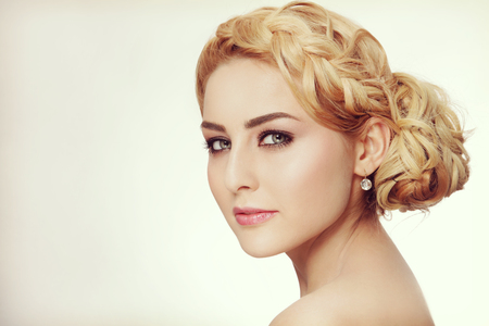 Vintage style portrait of young beautiful blond woman with fancy prom hairdo and smoky eyes make-up