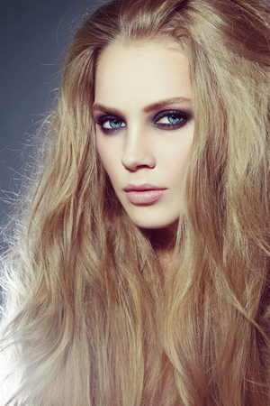 smoky eyes: Vintage style portrait of young beautiful woman with long hair and smoky eyes make-up Stock Photo