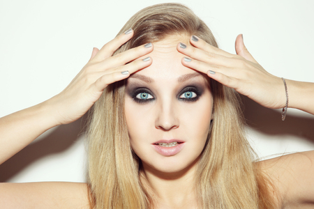 Portrait of young attractive blond woman touching her wrinkled forehead with worried expression Stock Photo