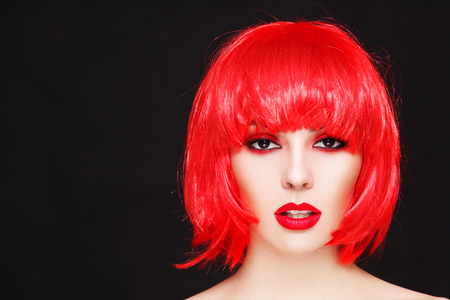 Portrait of young beautiful sexy girl with stylish make-up and fancy bob style red wig Stock Photo