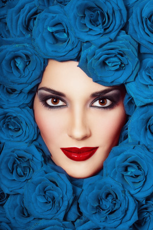 Vintage style close-up portrait of beautiful young girl with smoky eyes and fancy blue roses around her face photo
