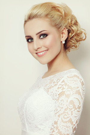 Vintage style portrait of young beautiful blond woman with stylish prom hairdo and smoky eyes