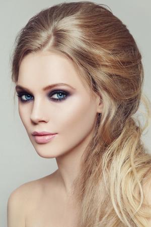 bollos: Retrato de joven bella mujer con los ojos ahumados maquillaje y el peinado desordenado estilo Foto de archivo
