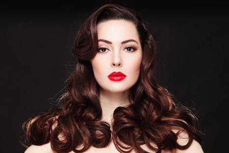 Portrait de la belle jeune femme aux longs cheveux bouclés et rouge à lèvres rouge