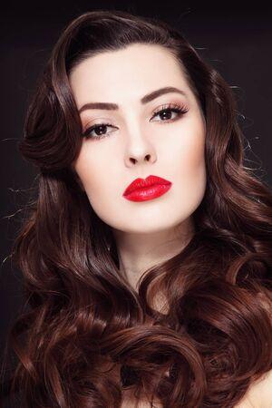 Retrato de joven bella mujer con el pelo largo y rizado y lápiz labial rojo