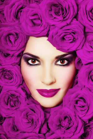 Vintage style close-up portrait of beautiful young girl with smoky eyes and purple roses around her face photo