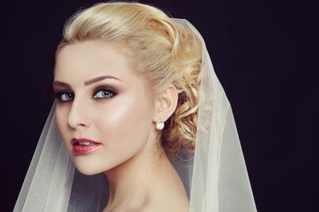 Retrato del estilo de la vendimia de la novia hermosa joven con los ojos ahumados maquillaje y velo de novia