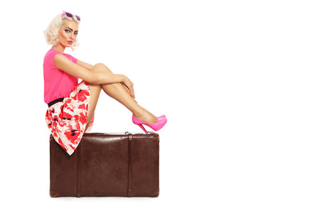 hot pink: Beautiful sexy blonde pin-up girl in mini skirt and hot pink shoes sitting on big vintage bag over white background