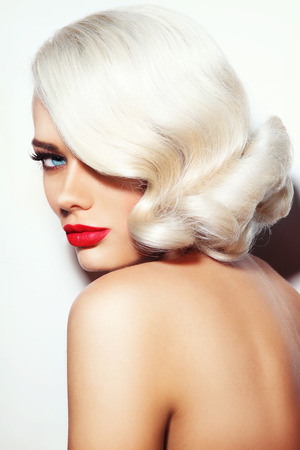 platinum hair: Portrait of young beautiful platinum blonde tanned woman with vintage hairdo and red lipstick