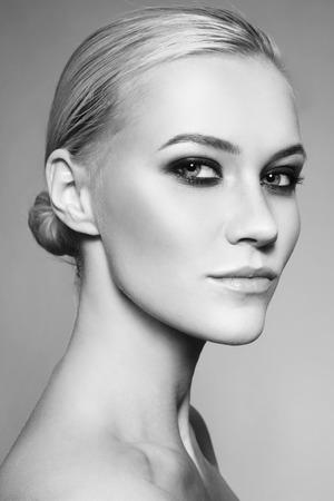 maquillaje de ojos: retrato en blanco y negro de la joven y bella chica con estilo del ojo de maquillaje ahumado y moño